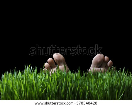 Toes and Feet of a Person Laying in Lush Green Grass at Night - stock photo