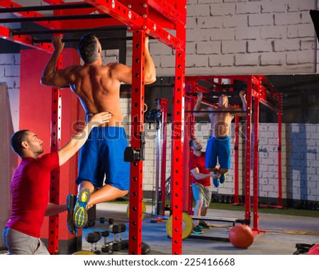Toes to bar man pull-ups personal trainer 2 bars workout - stock photo
