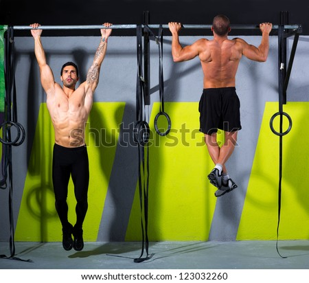 toes to bar men pull-ups 2 bars workout exercise at gym - stock photo