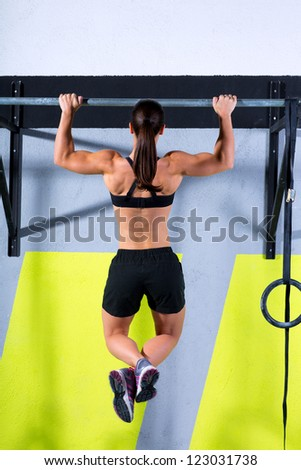 toes to bar woman pull-ups 2 bars workout exercise at gym - stock photo