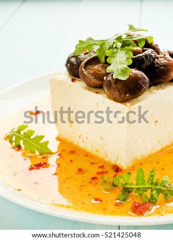 Tofu cheese with marinated shiitake mushrooms in carrot sauce. Shallow dof.