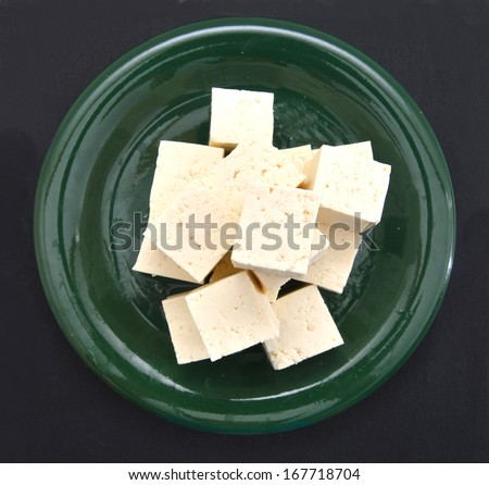 Tofu cubes on plate isolated on black background - stock photo