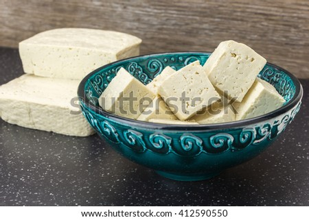 Tofu cut into cubes in bowl and blocks, on wooden background. - stock photo