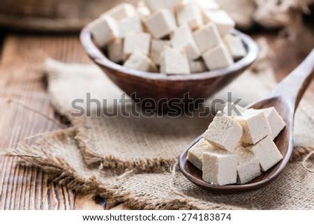 Tofu (detailed close-up shot) on wooden background - stock photo