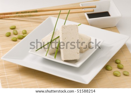 Tofu on a white plate. Fresh soy beans on foreground. - stock photo