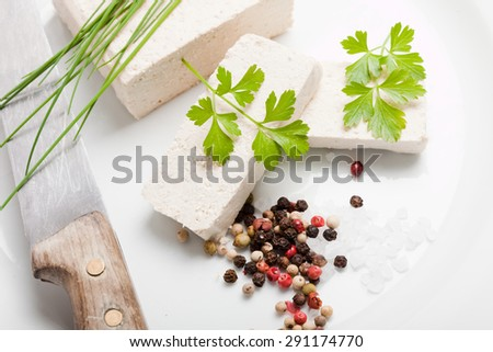 tofu slices with parsley, salt, pepper and chives on white plate, with old knife - stock photo