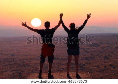 Together in wondering world. Young man and girl holding hands up, standing on the mountain top against sunset. People, love, nature and travel concept
