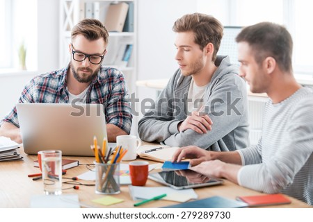 Together they will figure it out. Three young confident men working together while sitting at their working place in office - stock photo