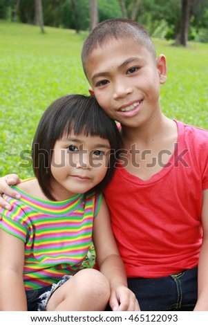 Together, two asian kids having a good time in the park, spring time.
