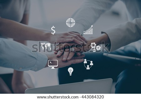Together we are stronger! Close-up part of top view of group of four young people holding hands and showing their unity while sitting at office - stock photo