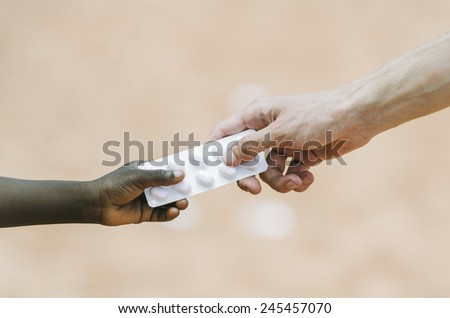 Togetherness: Handing Drugs to African Children (Giving Pills to Cure) - stock photo