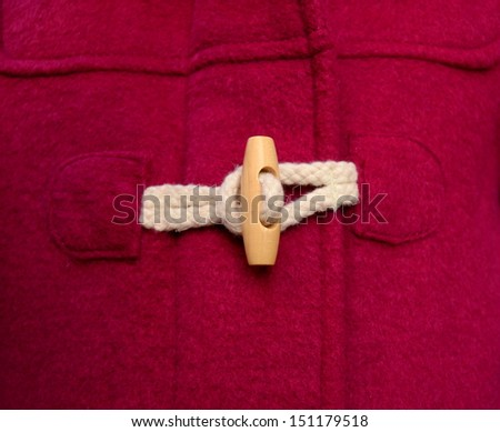 Toggle Button On A Red Duffle Coat - stock photo