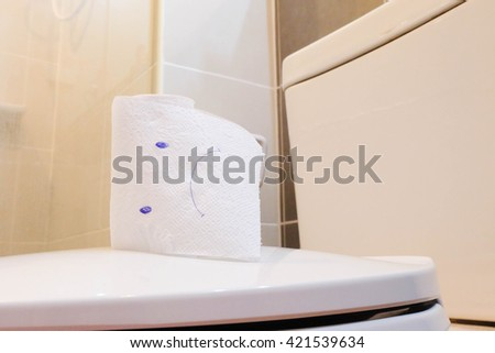 Toilet bowl and bad face drawings on toilet paper. - stock photo