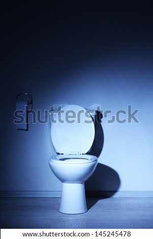 Toilet bowl in a bathroom with blue light - stock photo