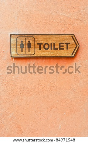 Toilet direction board on the orange wall. - stock photo