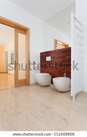 Toilet in bright bathroom with opened door - stock photo