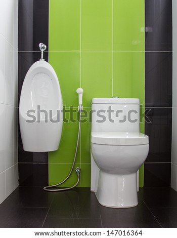 Toilet in gray and green tiled bathroom - stock photo