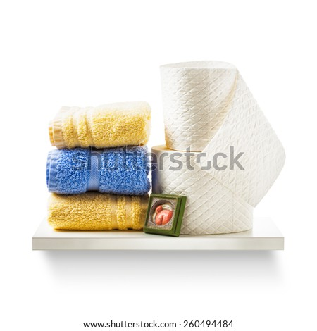 Toilet paper rolls and bath towels on shelf isolated on white background. Bathroom cabinet. Object with clipping path - stock photo