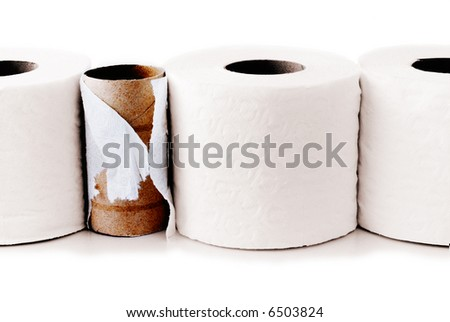 Toilet paper rolls in a row with a used up one among them - stock photo