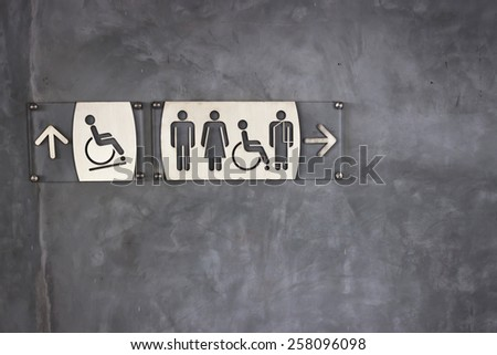 Toilet sign and direction on exposed concrete wall background - stock photo