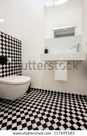 Toilet with a black and white tiles