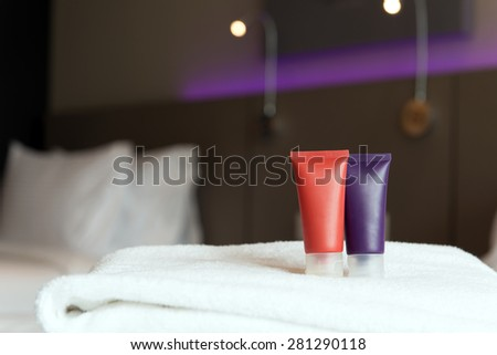 Toiletries on the towels inside hotel bedroom - stock photo