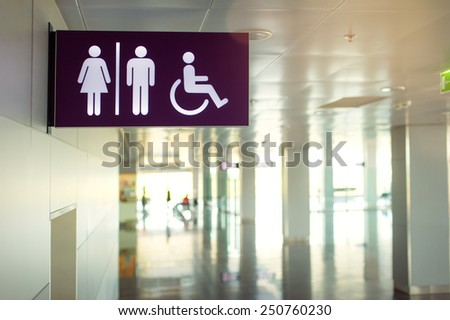 Toilets icon. Public restroom signs with a disabled access symbol. Interior of airport terminal. - stock photo