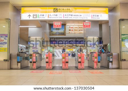 TOKYO - APRIL 9 : Japanese walking through a ticket gate in Shinjuku, Tokyo on April 9, 12. With more than 1.5 million passengers per day, Shinjuku is the biggest station in the world. - stock photo