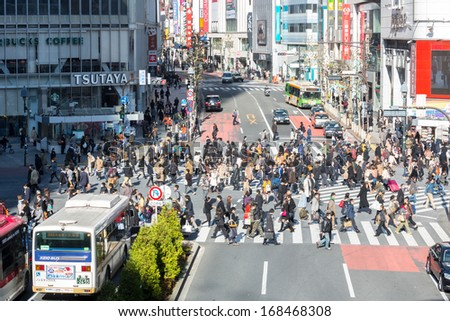 TOKYO - DECEMBER 11: Pedestrians cross at Shibuya Crossing December 11, 2013 in Tokyo, Japan. The crosswalk is one of the world's most famous implementations of a scramble crosswalk. - stock photo