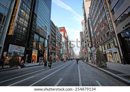 TOKYO - DECEMBER 21, 2014: Shoppers on the main street at Ginza Shopping district in Tokyo, Japan. Ginza is recognized as one of the most luxurious shopping districts in the world. - stock photo