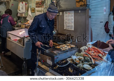 Tokyo, Japan - April 10: An unidentified man cooks seafood in one of the small shops located in the outer area of the Tsukiji Fish Market, in Tokyo, Japan; on April 10, 2015
