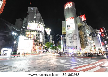 TOKYO, JAPAN - APRIL 13, 2014: Pedestrians walk at Shibuya Crossing during the holiday season. The scramble crosswalk is one of the largest in the world.