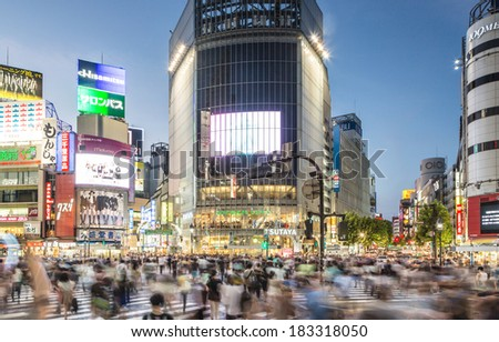 Tokyo, Japan - August 18 2013: A large group of people captured with motion blur walks through the world famous Shibuya crossing in Tokyo at dusk.  - stock photo