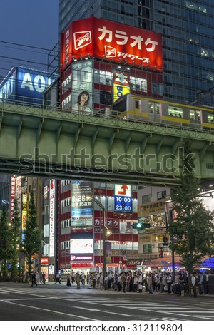 TOKYO, JAPAN - AUGUST Evening rush hour traffic in Akihabara with the bright neon advertisements in the background shown on August 7, 2015 in Tokyo, Japan - stock photo
