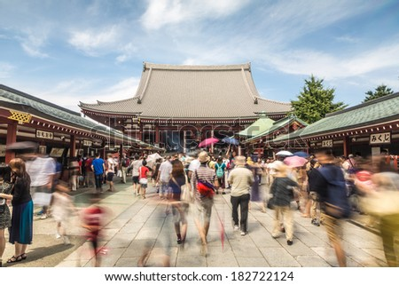 Tokyo, Japan - August 24 2013: People captured with motion blur walk along the entrance of the Buddhist temple Senso-ji in Tokyo.  - stock photo