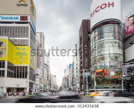Tokyo, Japan - August 24, 2013: People crossing the street with motion blur in the heart of Ginza, the place for luxury shopping in Tokyo, Japan - stock photo