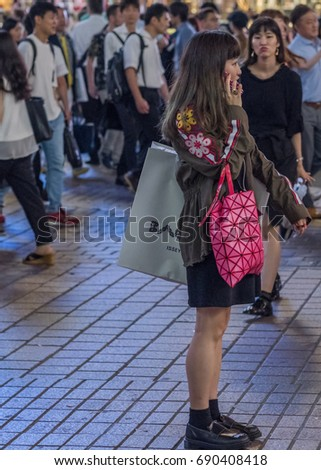 TOKYO, JAPAN - AUGUST 4TH, 2017.  Japanese girl with smartphone in Shibuya street.