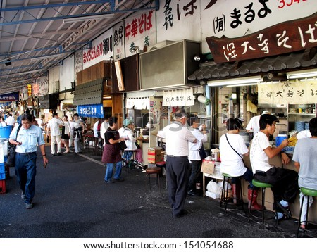 TOKYO, JAPAN- AUGUST 20, 2013: Tsukiji market is a large market for fish in central Tokyo. The market consists of small shops and restaurants crowded along narrow lanes. Tokyo, Japan. August 20 2013 - stock photo