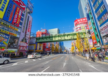 TOKYO, JAPAN - CIRCA JANUARY, 2016: Crowds pass below colorful signs in Akihabara. The electronic district has evolved into a shopping area for video games, anime, manga, computer January, 2016 Tokyo