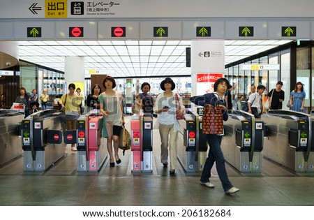 TOKYO, JAPAN - CIRCA JULY, 2014:People passing the gate. Commutor trains are the main mode of transportation in Tokyo. - stock photo