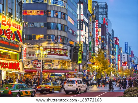 TOKYO, JAPAN - DECEMBER 15, 2012: Crowds walk under billboards in Shinjuku's Kabuki-cho district. The area is a nightlife district known as Sleepless Town.