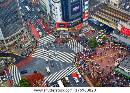 TOKYO, JAPAN - DECEMBER 15, 2012:  Traffic passes through Shibuya Crossing. The intersection is considered one of the world's busiest scramble crosswalks. - stock photo
