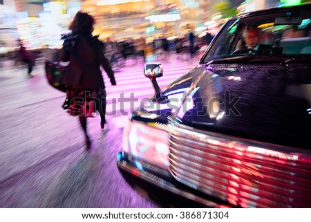 Tokyo, Japan - December 13, 2015: Woman passing through at  the Shibuya Crossing.  Shibuya Crossing rumoured to be the world`s busiest, this intersection is famously known as `The Scramble` - stock photo
