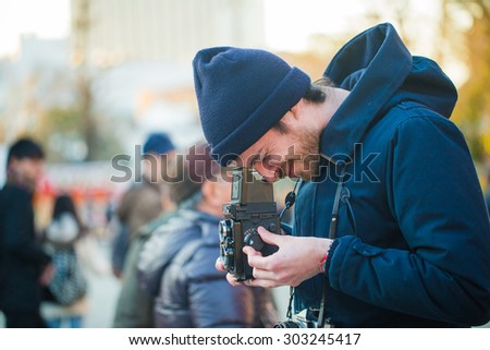 TOKYO, JAPAN - FEBRUARY 3, 2015: An unidentified man is taking photo with Yashica vintage film camera in Sensoji Temple, Asakusa.