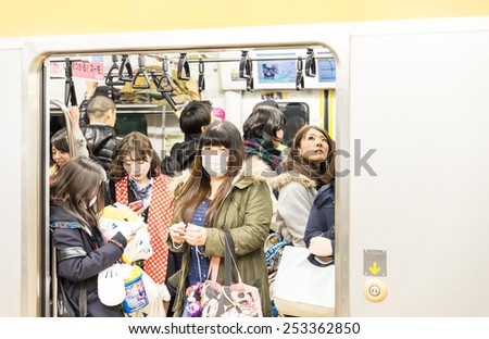 TOKYO,JAPAN - FEBRUARY 10,2015: people in a subway train wagon. The transit system carries almost an average of 8 million passengers daily. - stock photo