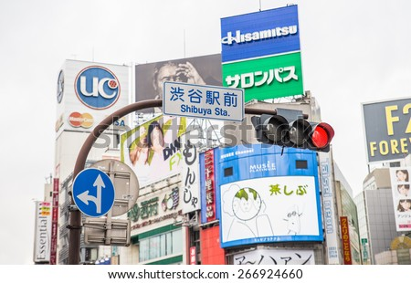 TOKYO, JAPAN - FEBRUARY 10,2015: Street signs and billboards at Shibuya Crossing,Tokyo. The scramble crosswalk is one of the largest in the world. - stock photo
