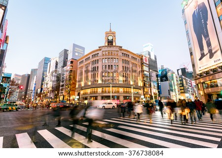 Tokyo, Japan - January 18, 2015:  Ginza shopping district at rush hour in Tokyo. The iconic Ginza Wako building is at the background.  - stock photo