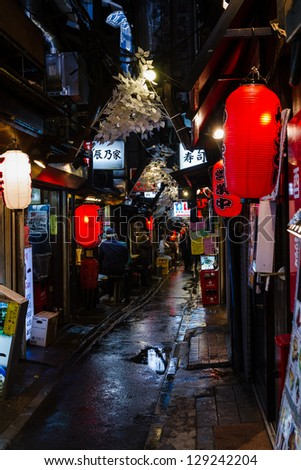 TOKYO,JAPAN - JANUARY 16: Narrow pedestrian street known as Yakatori alley in the old Shinjuku district in Tokyo, Japan on the night of January 16, 2011. A few traditional restaurants are located here - stock photo