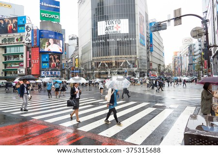 TOKYO, JAPAN - JANUARY 20 2016: People acrossing the crosswalk in raining day on March 20, 2014.Shibuya crossing is one of busiest places in Tokyo - Motion blurred. - stock photo