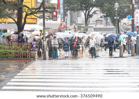 TOKYO, JAPAN - JANUARY 20 2016: People acrossing the crosswalk in raining day on March 20, 2014.Shibuya crossing is one of busiest places in Tokyo - Montion blurred. - stock photo